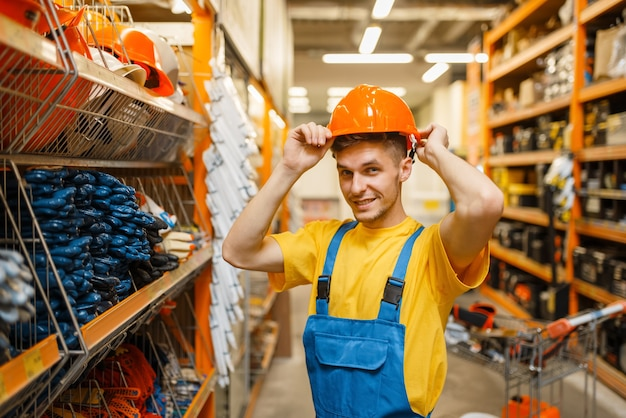 Male builder trying on helmet at the shelf in hardware store. constructor in uniform look at the goods in diy shop