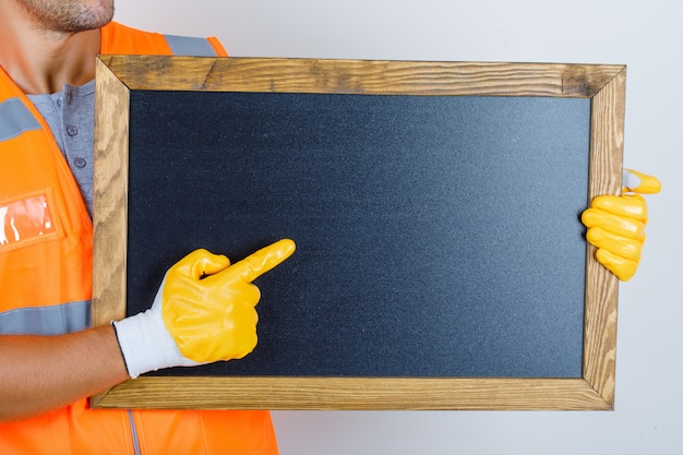 Male builder in uniform, gloves showing something on blackboard, front view.