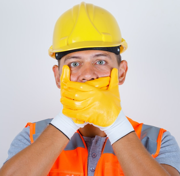 Male builder in uniform, helmet, gloves covering mouth with hands for mistake and looking shocked, front view.