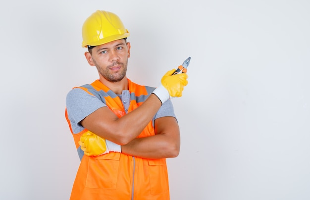 Male builder in uniform, helmet, gloves holding pliers, front view.