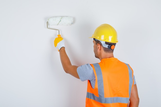 Male builder in uniform, helmet, gloves painting wall with roller, back view.