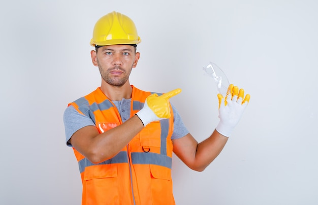 Male builder in uniform, helmet, gloves pointing safety glasses with finger, front view.