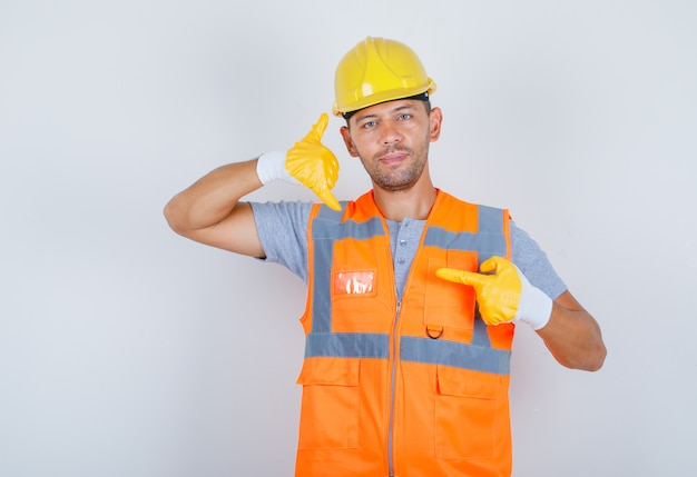 Male builder in uniform, helmet, gloves showing call me or contact gesture and looking confident, front view.