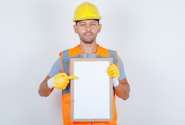 Male builder in uniform, helmet, gloves showing something on white board, front view.