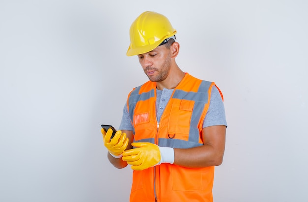 Male builder in uniform, helmet, gloves using mobile phone and looking busy, front view.