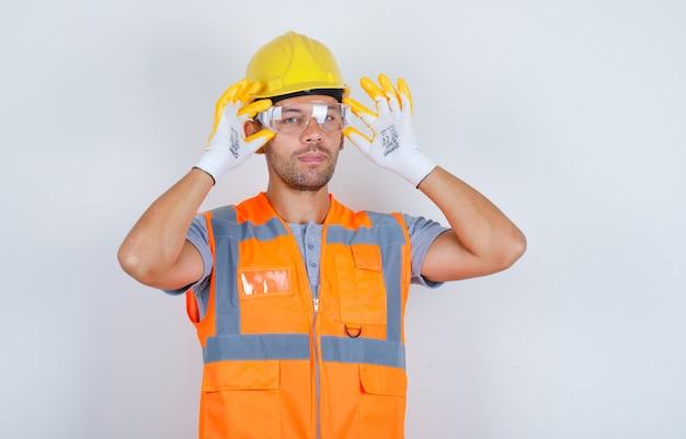 Male builder in uniform, helmet, gloves wearing safety glasses, front view.