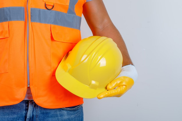 Male builder in uniform, jeans, gloves holding helmet in his hand, front view.