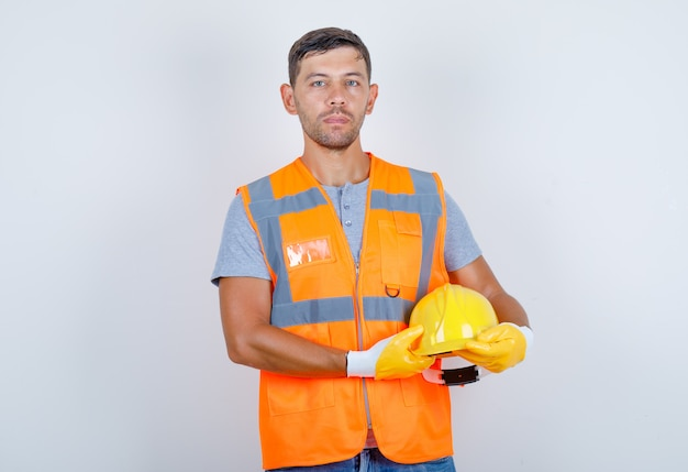 Male builder in uniform, jeans, gloves holding helmet in his hands, front view.