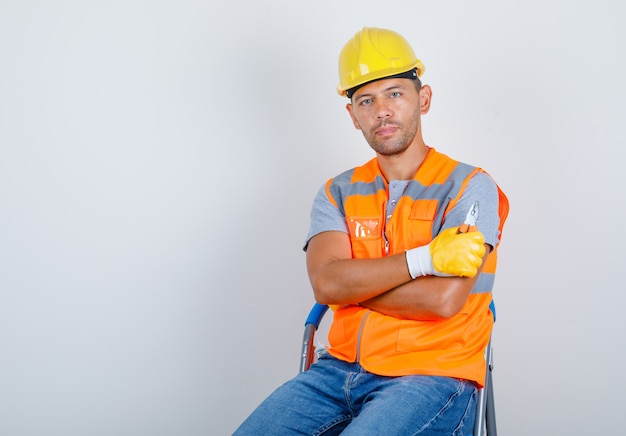 Male builder in uniform, jeans, helmet, gloves sitting with crossed arms, front view.