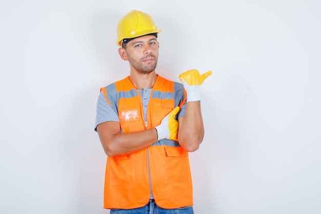 Male builder in uniform pointing away while standing and looking confident, front view.
