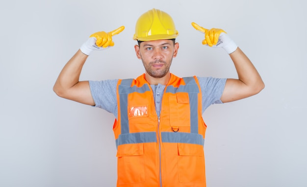 Male builder in uniform pointing fingers at security helmet and looking confident, front view.
