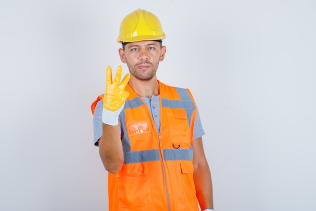 Male builder in uniform pointing up with fingers number three, front view.