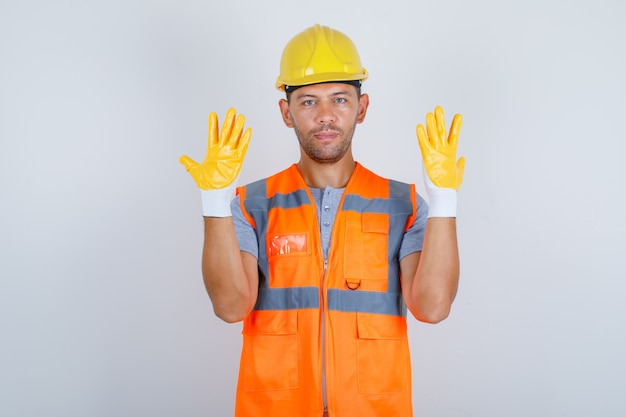 Male builder in uniform raising hands and showing fingers, front view.