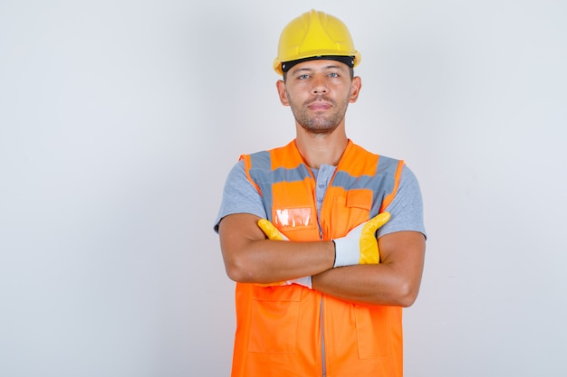 Male builder in uniform standing with crossed arms and looking confident, front view.