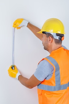 Male builder using measuring tape in uniform, helmet, gloves and looking busy, back view.