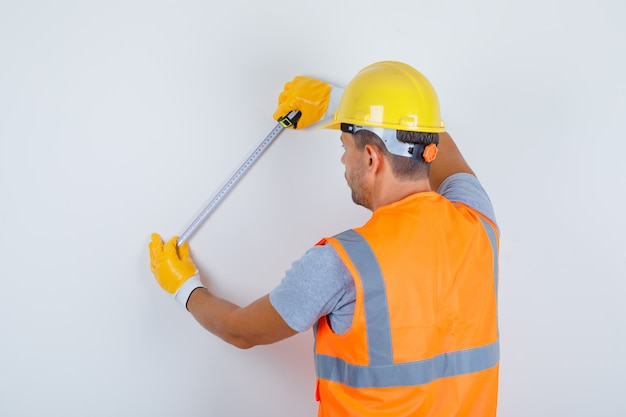 Male builder using measuring tape on wall in uniform, helmet, gloves and looking busy, back view.