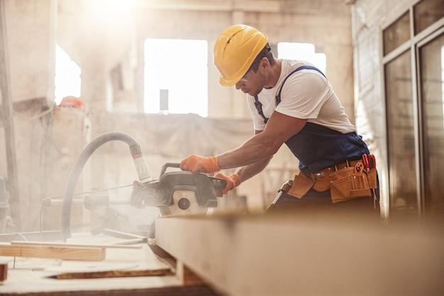 작업장에서 나무 절단 원형 톱 기계를 사용하는 남성 건축업자