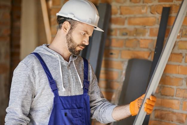 Строитель-мужчина в комбинезоне и каске держит металлический стержень для гипсокартона на внутренней строительной площадке
