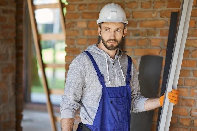 Мужчина-строитель в комбинезоне и каске смотрит в сторону, держа металлическую шпильку для гипсокартона