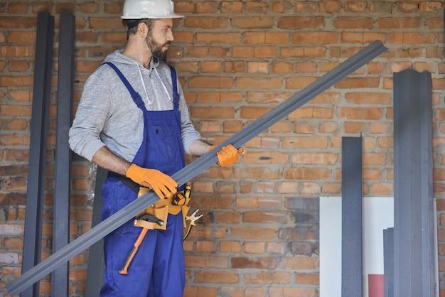 Мужчина-строитель в комбинезоне и каске выглядит сосредоточенным, держа металлическую шпильку для гипсокартона