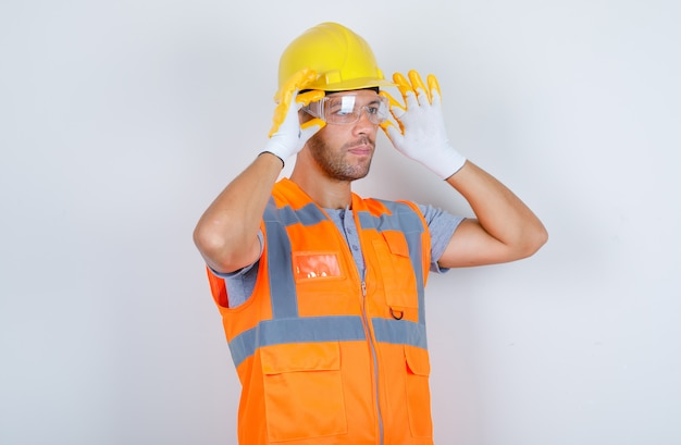 Male builder wearing safety glasses in uniform, helmet, gloves, front view.