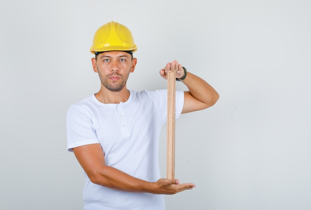 Male builder in white t-shirt, security helmet holding wooden ruler, front view.