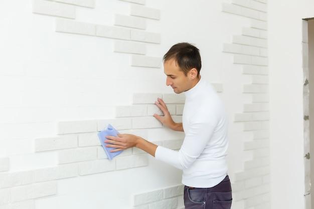 男性ビルダーは修理後に壁のレンガタイルを拭きます