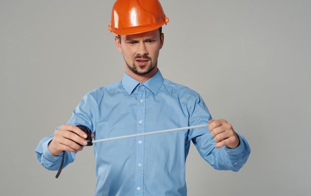 회색에 그의 손에 측정 테이프를 가진 남성 작성기.