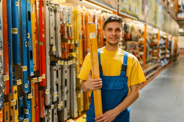 Male builder with building level in hardware store. constructor in uniform look at the goods in diy shop