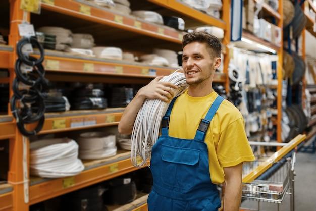 Мужчина-строитель с катушкой проводов в строительном магазине. конструктор в униформе осматривает товары в магазине своими руками