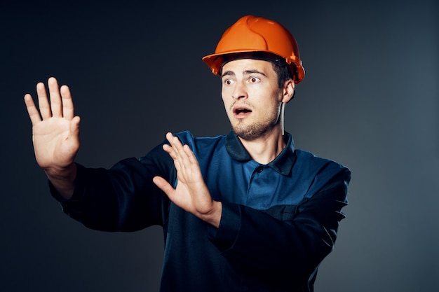 Male builder in work clothes and a miner's helmet