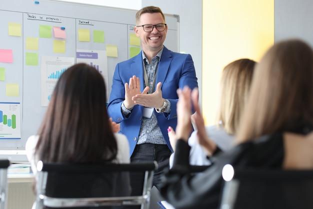 Мужской бизнес-тренер и люди аплодируют в аудитории