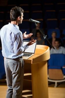 会議センターでスピーチをする男性経営者