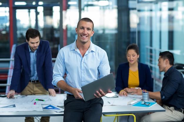 Мужской руководитель бизнеса держит ноутбук