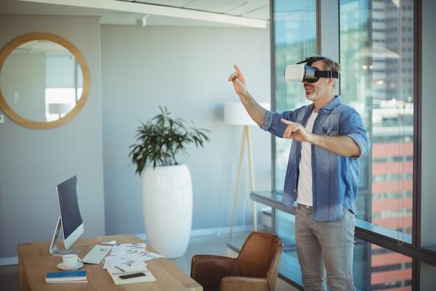 Мужской руководитель бизнеса с помощью гарнитуры виртуальной реальности