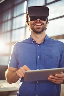 Male business executive in virtual reality headset using digital tablet