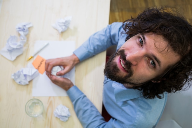 Male business executive with crumpled paper