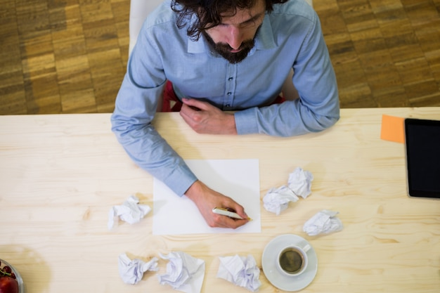 Male business executive writing on a blank paper