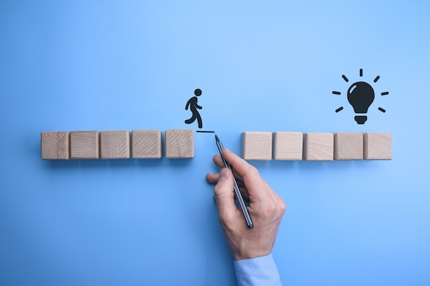 Male business man hand drawing a connecting line between two sets of wooden blocks for a silhouetted man to walk across.