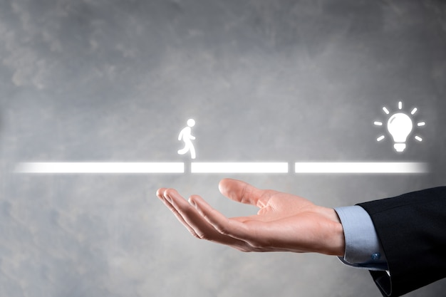 Male business man hand hold a connecting block between two sets of bridge road for a silhouetted man to walk idea icon.