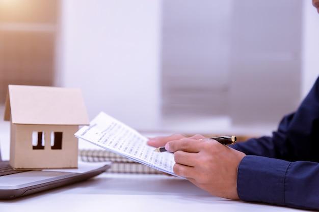 銀行と財務諸表を作るために文書を読む男性ビジネスマン。