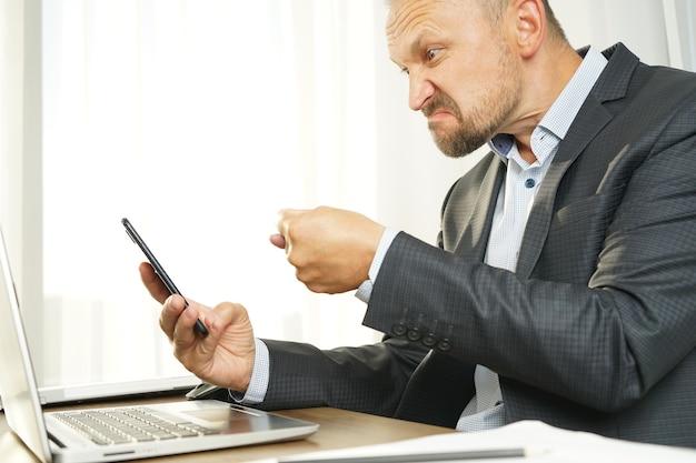 Мужчина-бизнесмен агрессивно выражает негативные эмоции при общении по видеосвязи