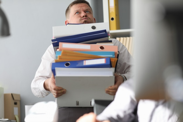 Male businessman carries a bunch of folders