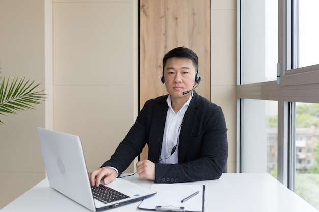 Male businessman conducts online training using a headset and laptop