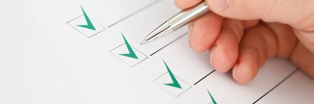 Мужской бизнесмен рука держать серебряную ручку и сделать зеленую галочку крупным планом