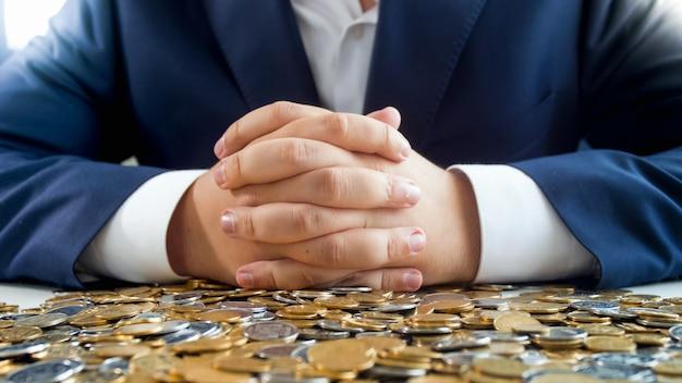 コインの山の上に横たわっている男性実業家の手。金融投資、経済成長、銀行貯蓄の概念。