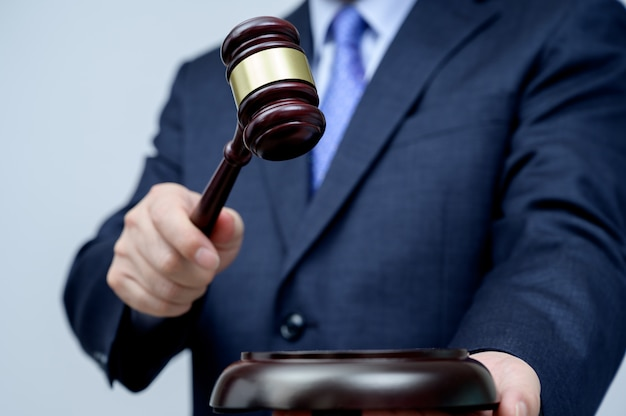 Male businessman holding a gavel in hand. justice and auction concept.