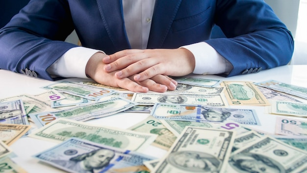 Мужской бизнесмен, взявшись за руки на столе, покрытом деньгами. концепция финансовых вложений, роста экономики и банковских сбережений.