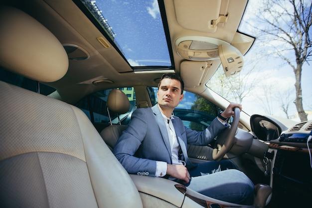 자동차의 바퀴 뒤에 앉아 비즈니스 정장에 남성 사업가