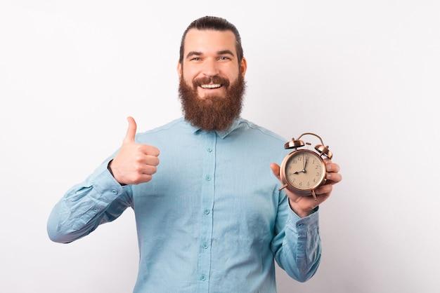 남성 사업가가 알람 시계를 들고 카메라를 향해 엄지손가락을 보이고 있습니다.